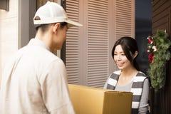 Mulher que recebe o pacote do homem de entrega Fotos de Stock