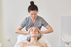 A mulher que recebe o tratamento dos termas, cosmetologist faz a massagem de cara para o cliente novo A fêmea bonita relaxa no sa imagem de stock royalty free