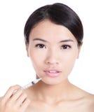 Mulher que recebe uma injeção do botox em seu bordo Fotografia de Stock Royalty Free
