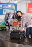 Mulher que recolhe a bagagem na correia transportadora no aeroporto Imagem de Stock