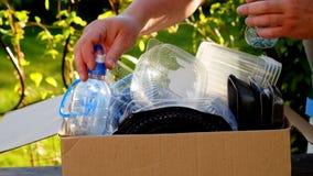 Mulher que recolhe garrafas e recipientes plásticos para reciclar filme