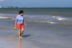 Mulher que recolhe shell na ressaca no Golfo do México Fotografia de Stock