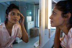 Mulher que reflete no espelho no banheiro imagem de stock royalty free