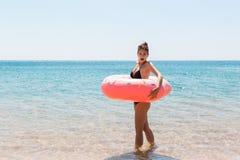Mulher que relaxa com anel inflável na praia menina chocada ou surpreendida no mar frio F?rias de ver?o e conceito das f?rias fotografia de stock