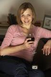 Mulher que relaxa com o vidro do vinho que presta atenção à tevê Fotografia de Stock Royalty Free