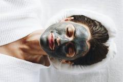 Mulher que relaxa com uma máscara do facial do carvão vegetal fotografia de stock