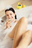 Mulher que relaxa com vidro do vinho no banho Imagens de Stock Royalty Free