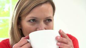 Mulher que relaxa em casa com bebida quente filme