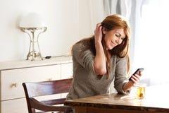 Mulher que relaxa em casa com telefone esperto foto de stock