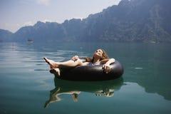 Mulher que relaxa em um anel de flutuação foto de stock