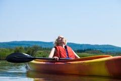 Mulher que relaxa em um caiaque e que aprecia sua vida Foto de Stock Royalty Free