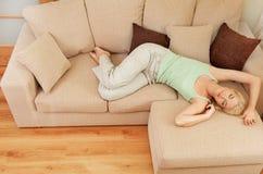 Mulher que relaxa em um sofá Fotografia de Stock