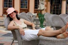 Mulher que relaxa em uma cadeira fotografia de stock