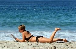 Mulher que relaxa em uma praia fotografia de stock