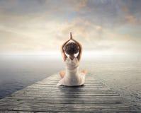 Mulher que relaxa fazendo a ioga