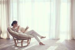 Mulher que relaxa na cadeira Fotografia de Stock Royalty Free