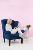 Mulher que relaxa na cadeira Foto de Stock Royalty Free