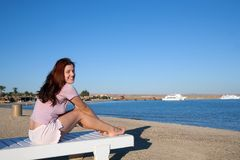 Mulher que relaxa na cadeira de plataforma imagens de stock royalty free