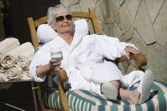 Mulher que relaxa na cadeira de sala de estar imagens de stock royalty free