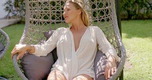Mulher que relaxa na cadeira de suspensão exterior no jardim filme