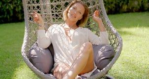 Mulher que relaxa na cadeira de suspensão exterior no jardim vídeos de arquivo