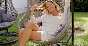 Mulher que relaxa na cadeira de vime fora no jardim vídeos de arquivo