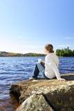 Mulher que relaxa na costa do lago Fotos de Stock