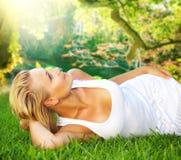 Mulher que relaxa na grama verde fotos de stock royalty free