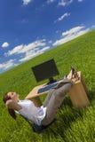 Mulher que relaxa na mesa de escritório no campo verde imagens de stock