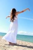 A mulher que relaxa na praia com braços abre a apreciação de sua liberdade Imagens de Stock Royalty Free