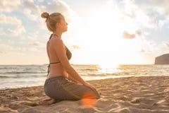Mulher que relaxa na praia do mar no por do sol Fotografia de Stock