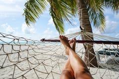 Mulher que relaxa na rede no paraíso tropical imagem de stock