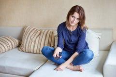 Mulher que relaxa na sala de visitas que guarda a televisão ou a tevê de controle remoto e olhando imagem de stock