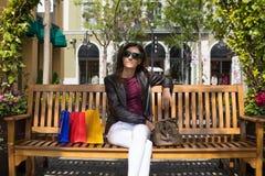 Mulher que relaxa no banco com os sacos de compras horizontais fotografia de stock