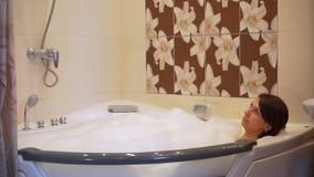 Mulher que relaxa no banho de espuma na banheira filme