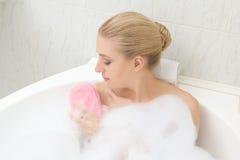 Mulher que relaxa no banho e que lava-se Foto de Stock Royalty Free