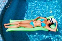 Mulher que relaxa no colchão na água da associação no dia ensolarado quente S foto de stock royalty free