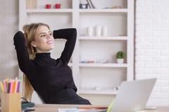 Mulher que relaxa no local de trabalho imagem de stock