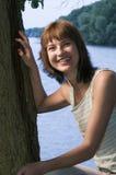 Mulher que relaxa pelo lago Imagem de Stock Royalty Free