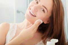 Mulher que remove a composição com a almofada do cotonete de algodão Foto de Stock Royalty Free