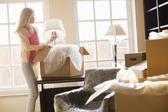 Mulher que remove a lâmpada de caixa movente na casa nova Imagens de Stock