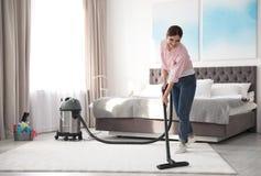 Mulher que remove a sujeira do tapete com o aspirador de p30 fotografia de stock
