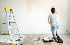 Mulher que renova a pintura de parede da casa imagem de stock