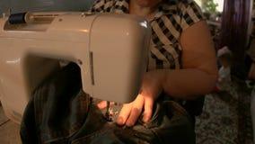 Mulher que repara calças de brim usando uma máquina de costura video estoque