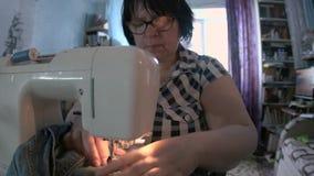 Mulher que repara calças de brim usando uma máquina de costura filme