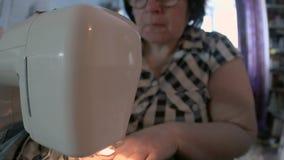 Mulher que repara calças de brim usando uma máquina de costura, tiro do close-up video estoque