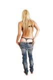 Mulher que retira calças de brim. Imagens de Stock