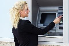 Mulher que retira o dinheiro do cartão de crédito Foto de Stock Royalty Free