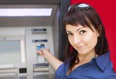 Mulher que retira o dinheiro do cartão de crédito no ATM imagem de stock