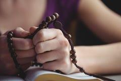 Mulher que reza com seus grânulos da Bíblia e do rosário imagens de stock